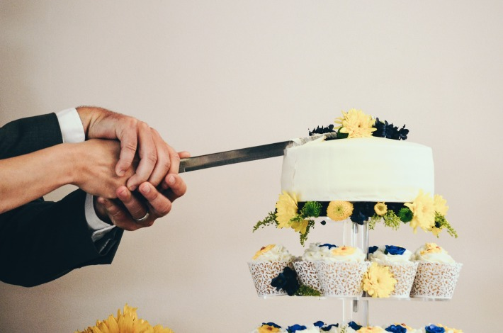 Photo d'un couple en train de découper leur gâteau de mariage
