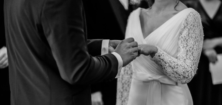 Photo d'un couple s'échangeant des alliances le jour de leur mariage civil à la mairie