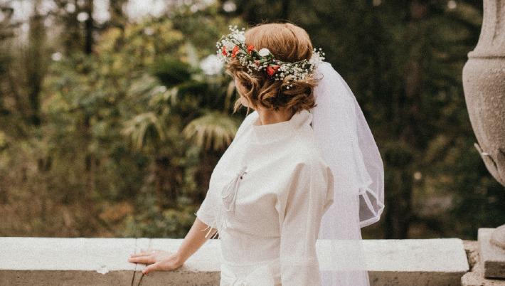 Photo d'une mariée au cocktail de son mariage devant un château