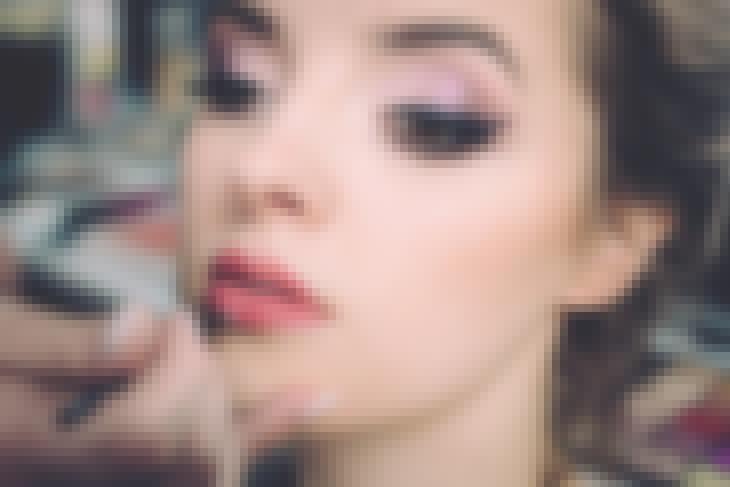 Visage d'une future mariée en train de se faire maquiller par une make up artist