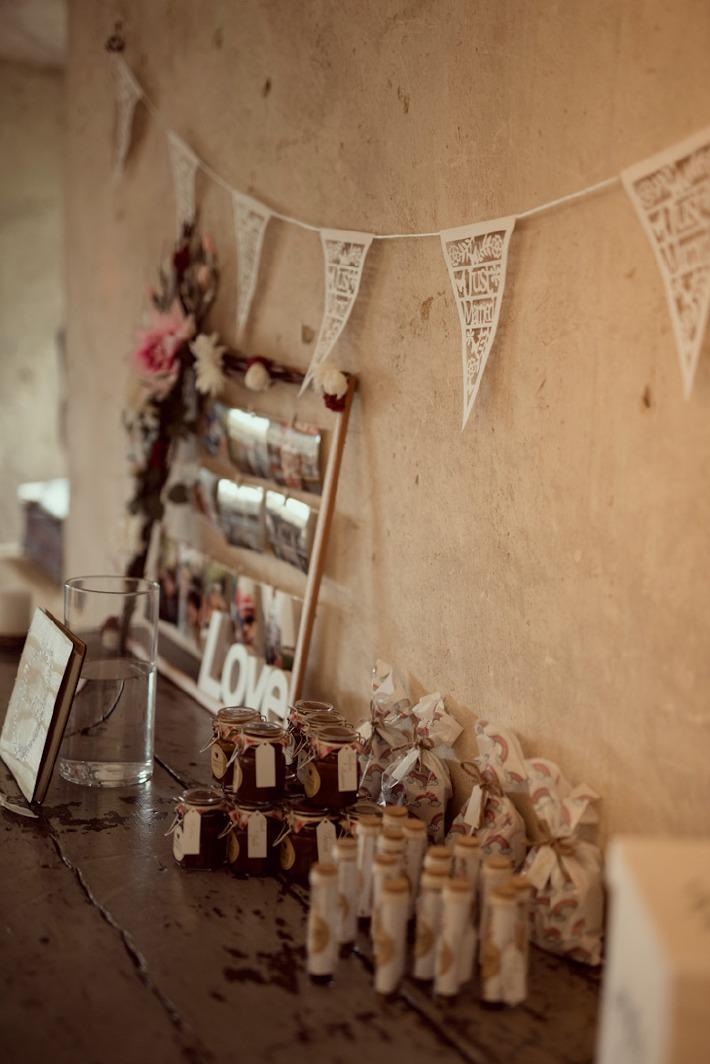 Décoration d'une table de mariage avec les cadeaux faits aux invités dans la grange du château de Bois Rigaud