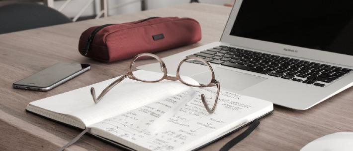Photo d'une personne en train d'**établir son budget de mariage** à l'aide d'un ordinateur et d'un carnet de note