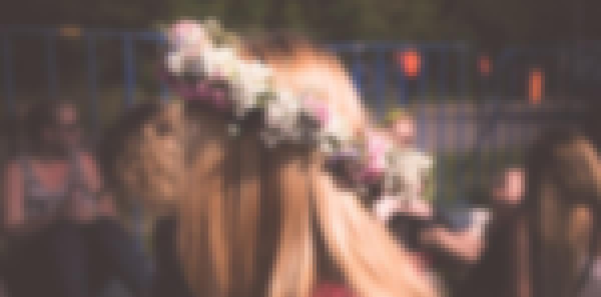 Une femme habillée en robe de mariée bohème chic pour son mariage avec une couronne de fleurs