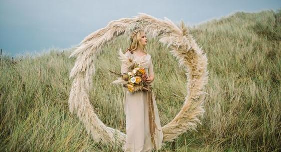 Photo d'une arche de mariage décorée avec des herbes de pampa pour un mariage bohème