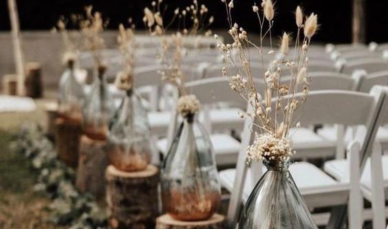 Photo d'une table décorée avec des dames-jeannes à l'occasion d'un mariage sur le thème bohème'