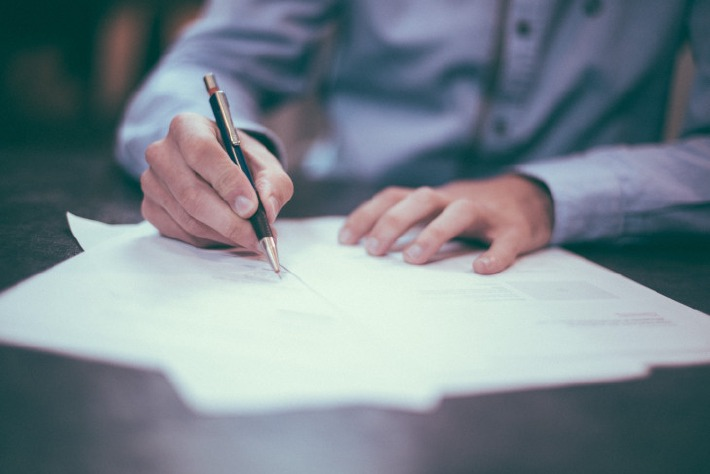 Personne signant un contrat avec un prestataire du mariage