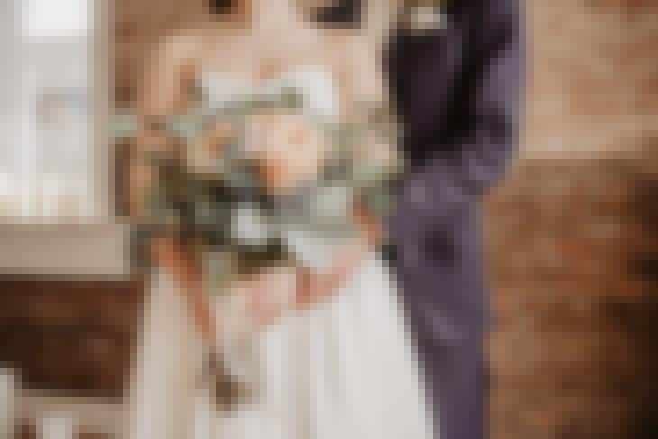 Couple de mariés avec un bouquet de fleurs à l'occasion de leur mariage