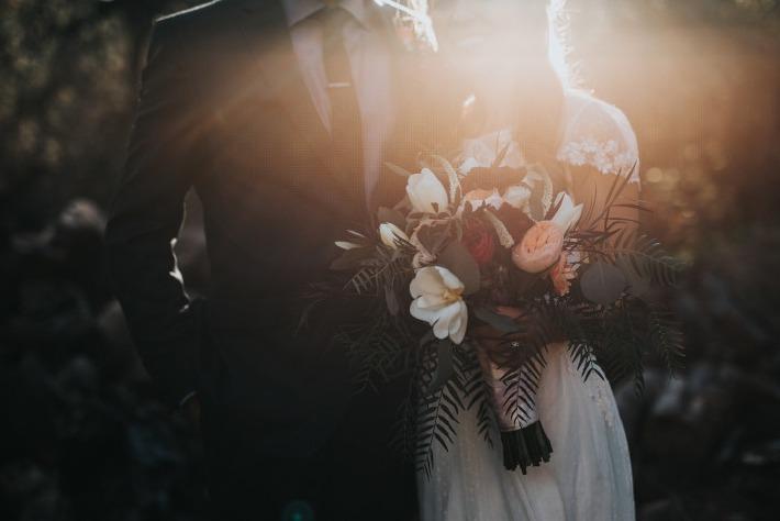 Couple de mariés portant un bouquet