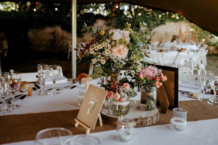 Décoration florale d'un mariage champêtre organisé sous une tente en extérieur au château de Bois Rigaud dans le Puy-de-Dôme