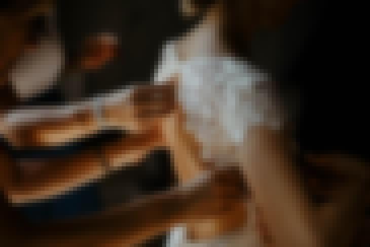 Photo d'une mariée en train d'enfiler sa robe de mariée