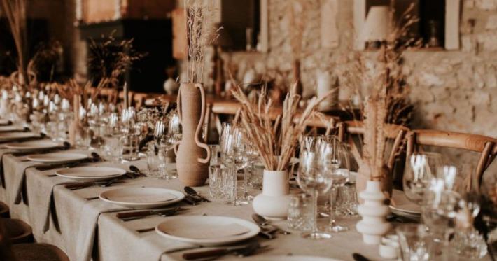 Photo d'une table de mariage rectangulaire et décorée avec de jolis articles de décoration dans un esprit champêtre et chic.