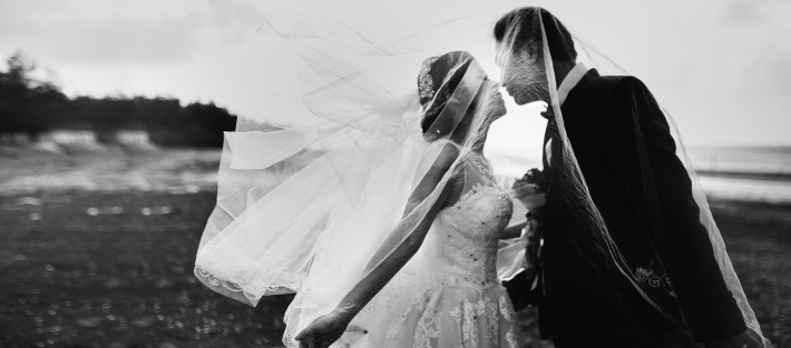 Picture of a couple kissing on their wedding day in France.