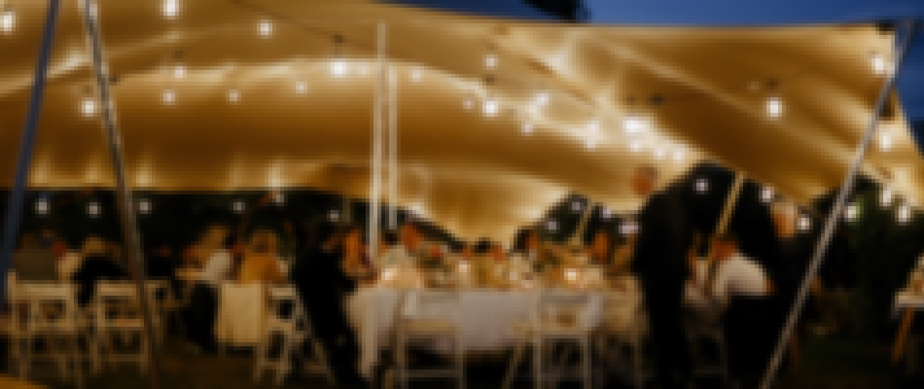 Alfresco wedding dinner under the marquee of Château de Bois Rigaud in the south of France