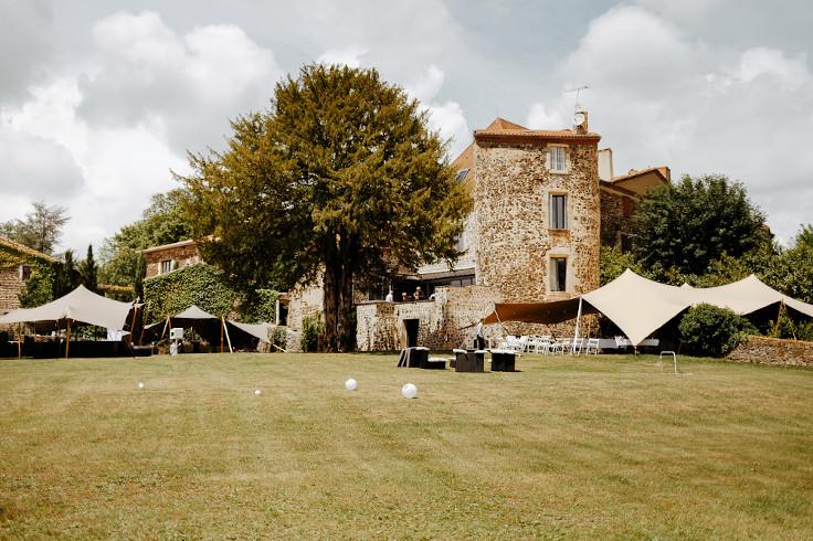 Photos des jardins du château de Bois Rigaud dans le Puy-de-Dôme en Auvergne, avec une vue sur la façade en pierres du château et sur ses tentes stretch extérieures